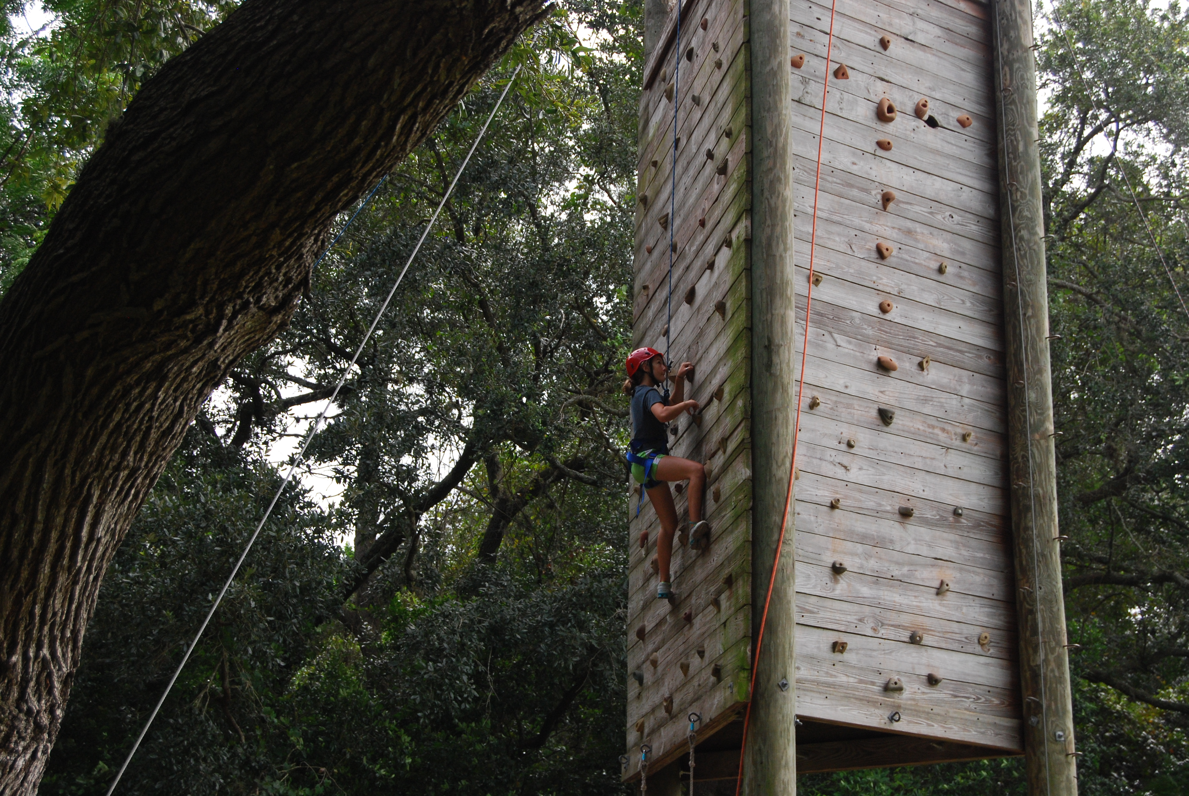 Young woman ascends climbing tower