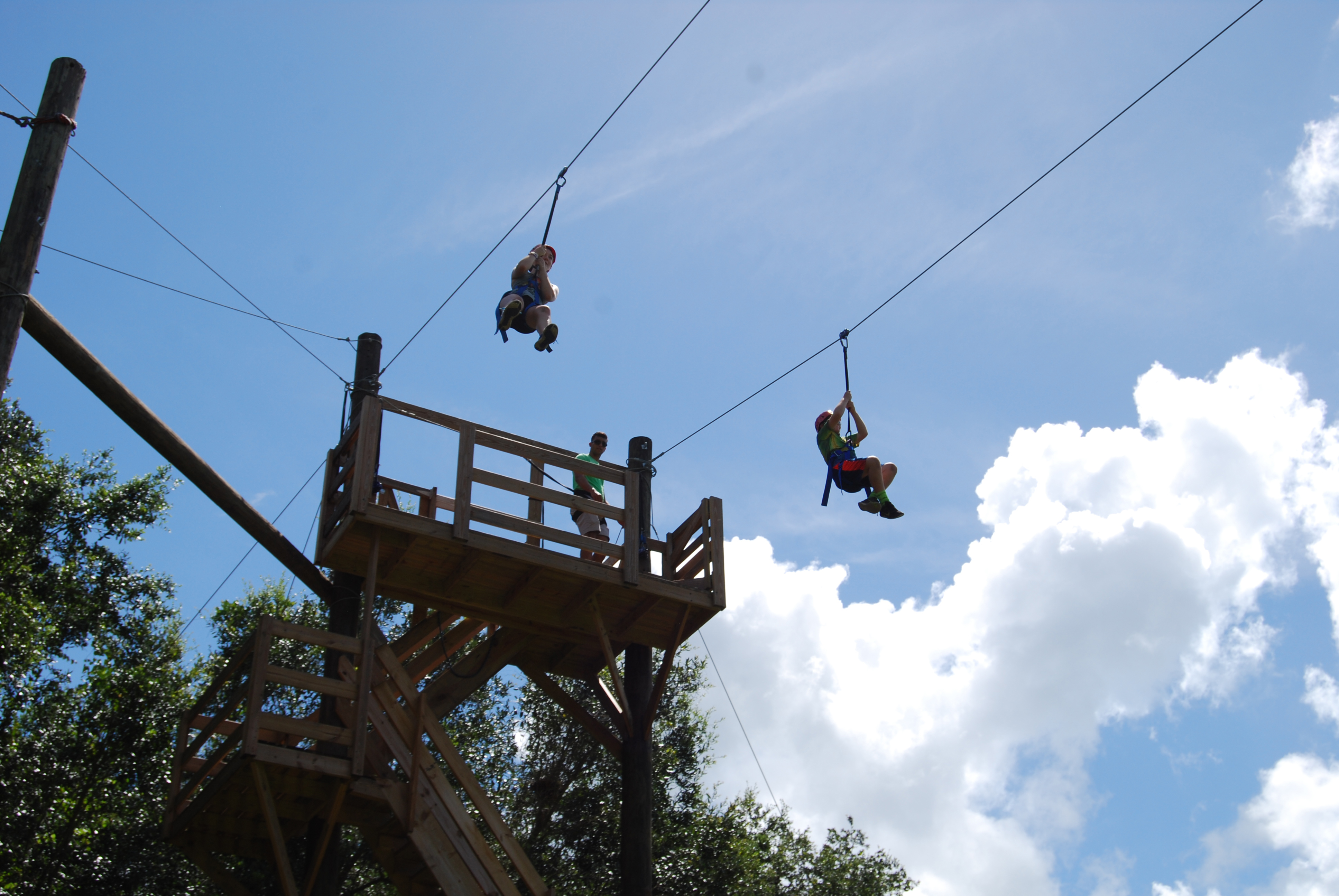 Participants lean on each other to complete high ropes course