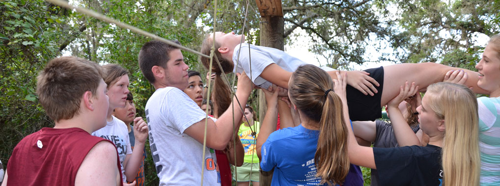 Participants collaborate on spider web challenge course element